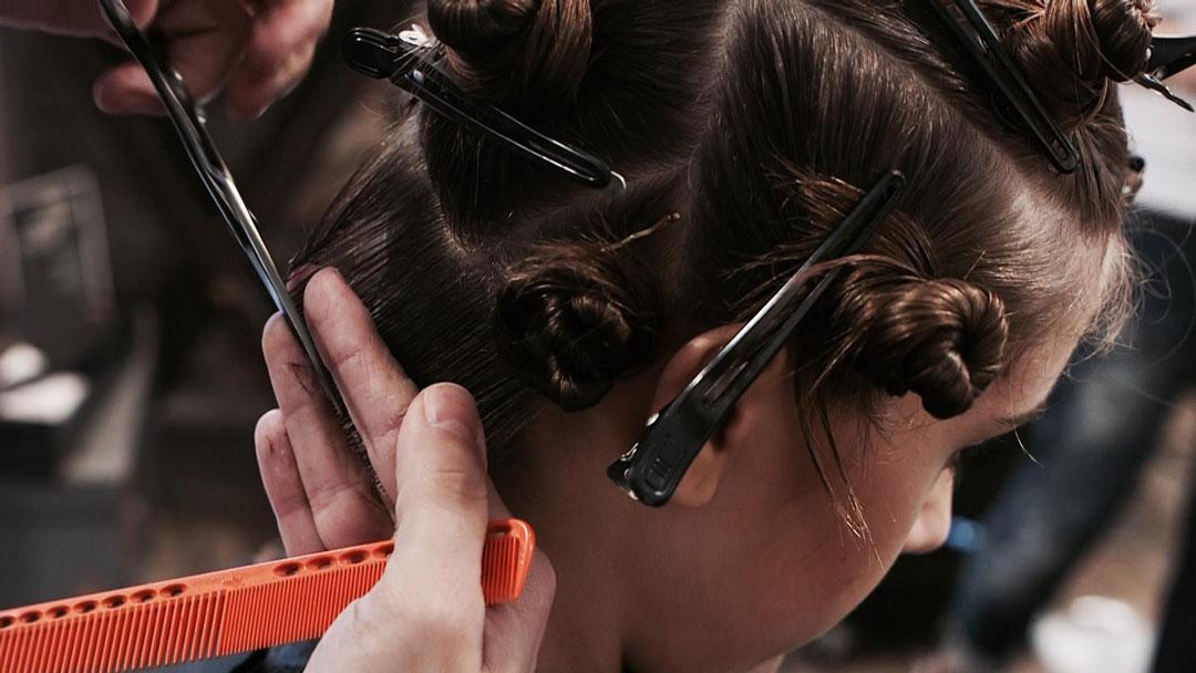 Primer plano de mano de peluquero cortando pelo a una cliente